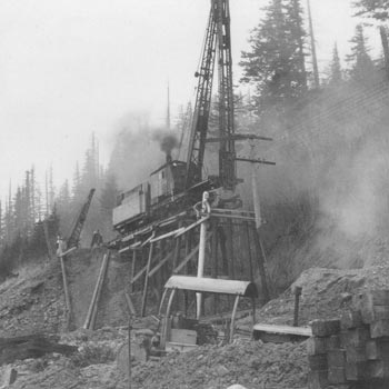 A pile driver builds a trestle during the construction of the Spokane, Portand & Seattle Railway
